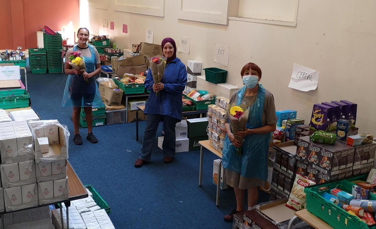 Volunteers at the CARIS Haringey foodbank, each holding a bunch of flowers