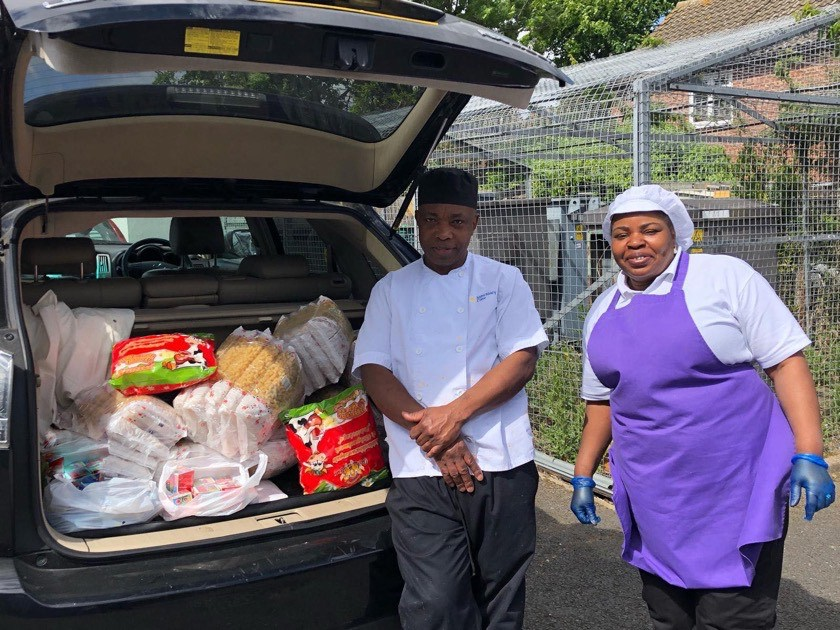 Van driver with food delivery and staff member at the food bank