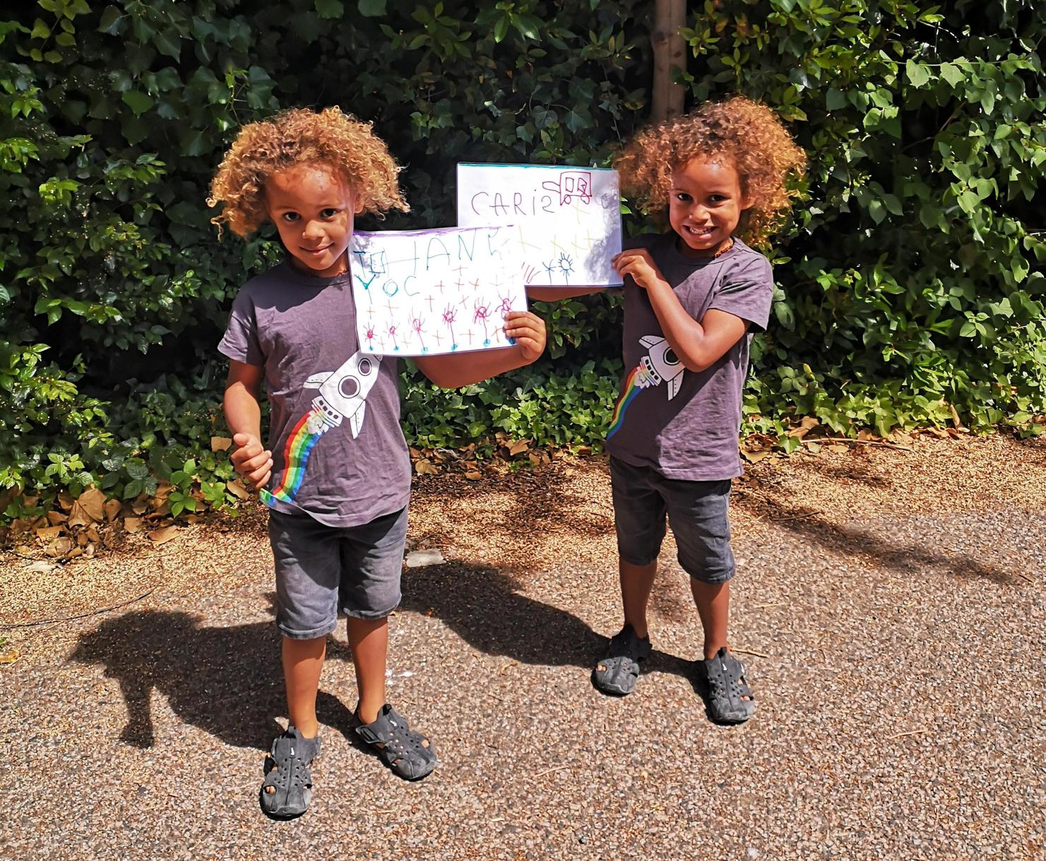Twin children with Thank You CARIS Haringey pictures they have created