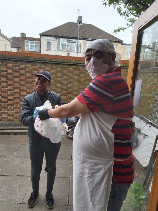RWCA Volunteer giving out  food parcel