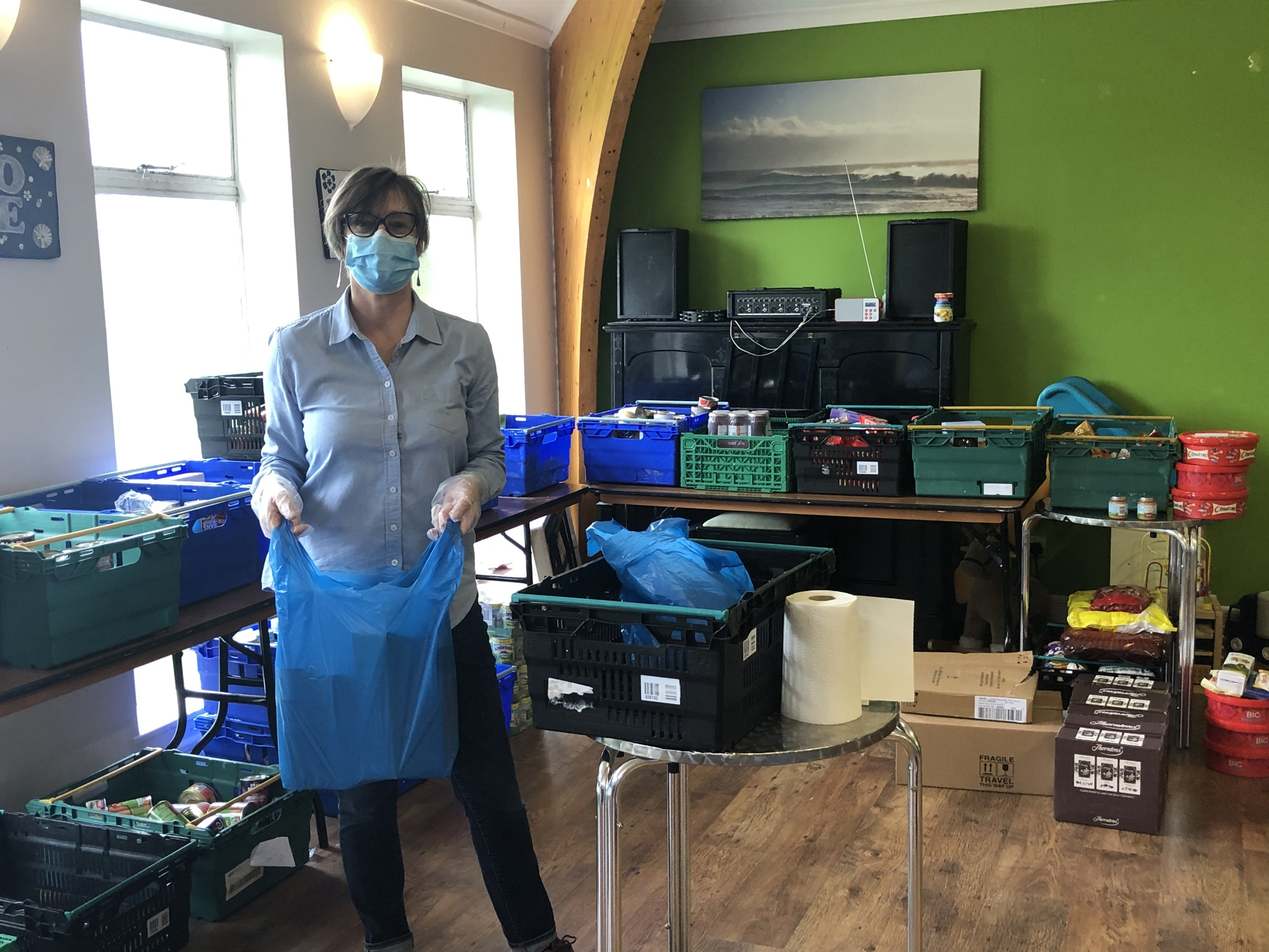 Muswell Hill Food Bank volunteer holding back of food and wearing a face mask