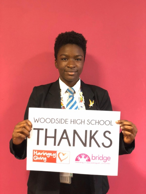 Jay at Woodside High School holding a card saying Thank You to Haringey Giving