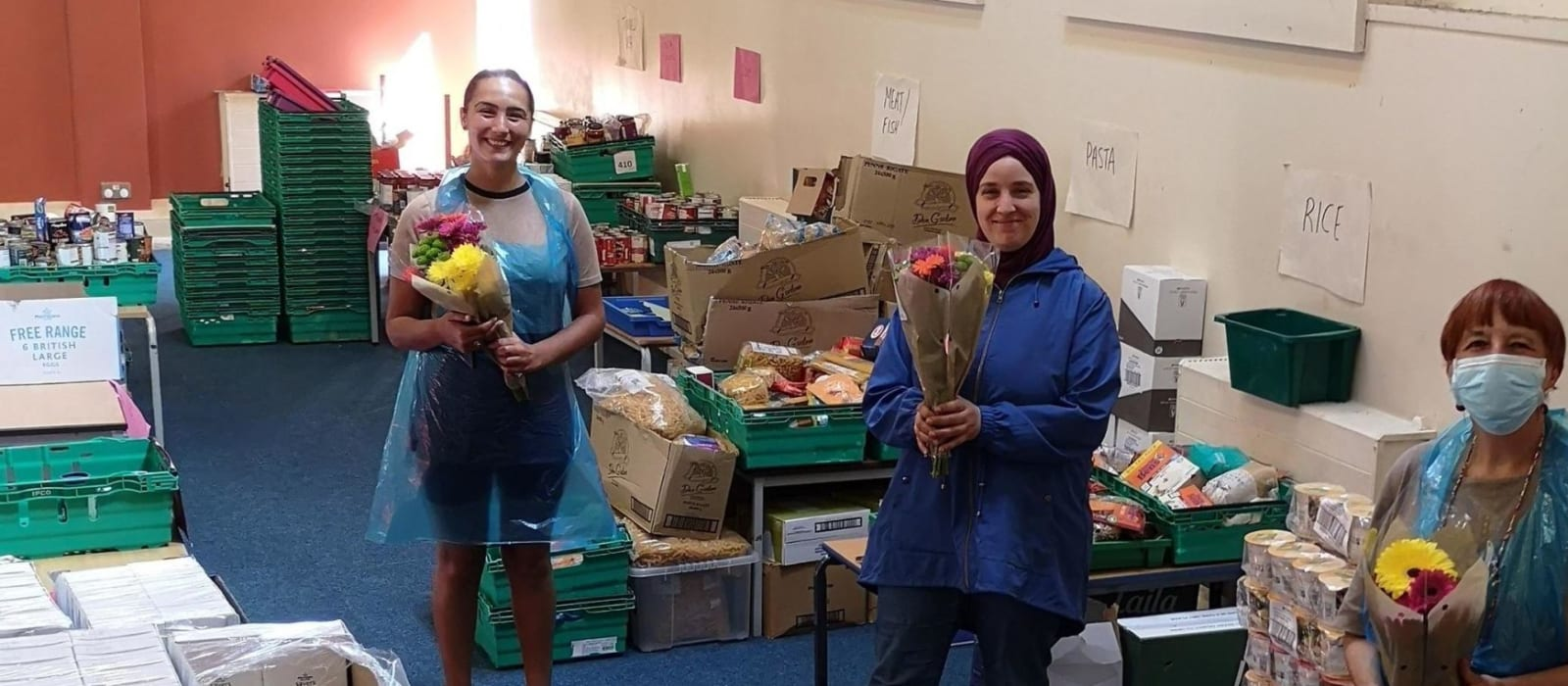 CARIS Volunteers at the foodbank, holding bunches of flowers