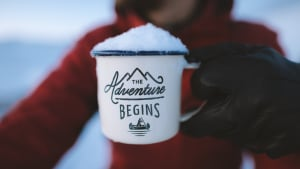 Adventure background with someone holding a mug which says The Adventure Begins