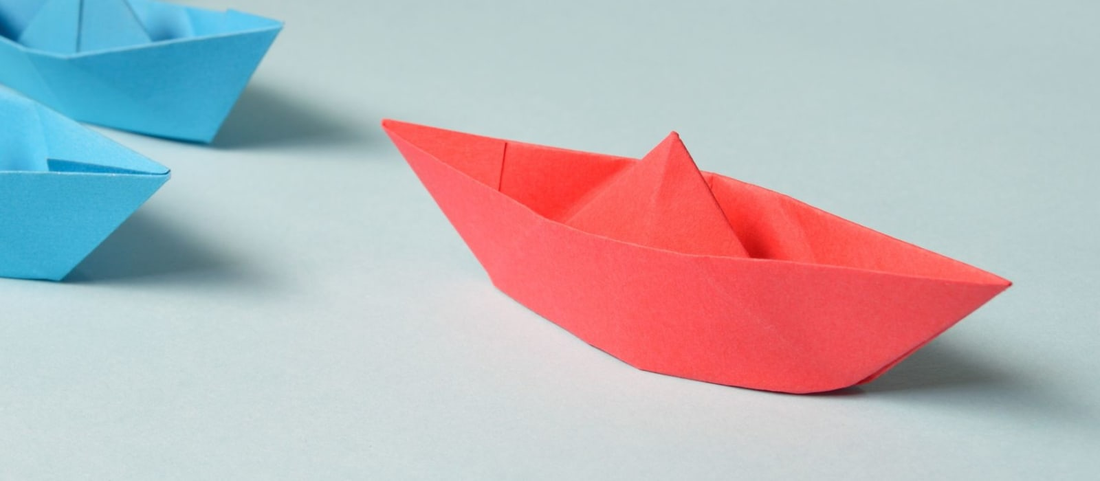 Paper boats - one larger red boat followed by four blue boats
